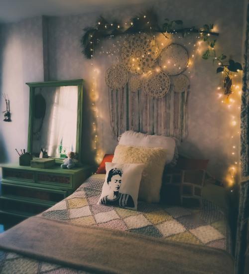 Parete dietro al letto con decorazioni boho